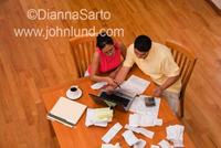 Picture of a hispanic or Latino couple seated together at the kitchen table paying their bills online. Receipts and bills litter the table top.